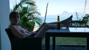 Emily with her feet up at the table with a beer overlooking the water in Tahiti