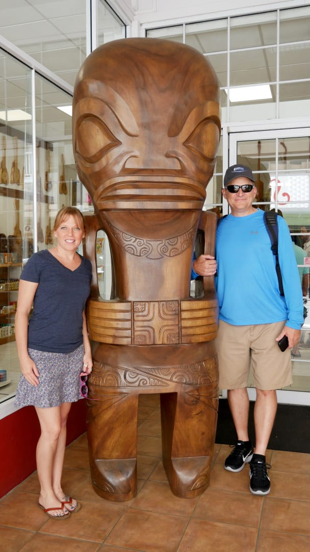 Emily and Lou standing with tall tiki statue