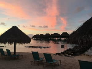 Water bungalows with orange sunset and beach