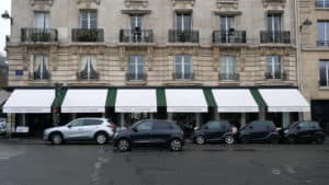 Cars parked on the side of the road with building windows symmetrical