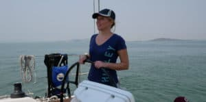 Emily at the helm of a sailboat