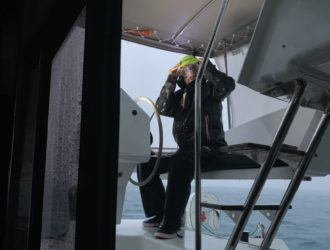 Matt at the helm of Sea Odyssey with goggles on looking scared