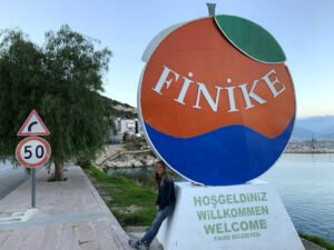 Emily leaning on Finike City Sign